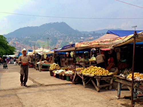 Man walking next to fruit stands at The Mercado Market in Tegucigalpa, Honduras